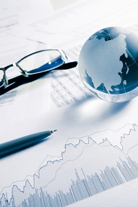 Arrangement of globe, glasses and pen on stock charts